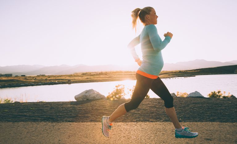 Pregnant woman running at sunrise